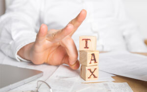 Businessman removes wooden blocks with the word Tax. Reduction o